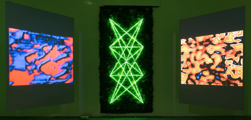 Three different projections of bright colored shapes with a neon green pattern against a black background in the middle.