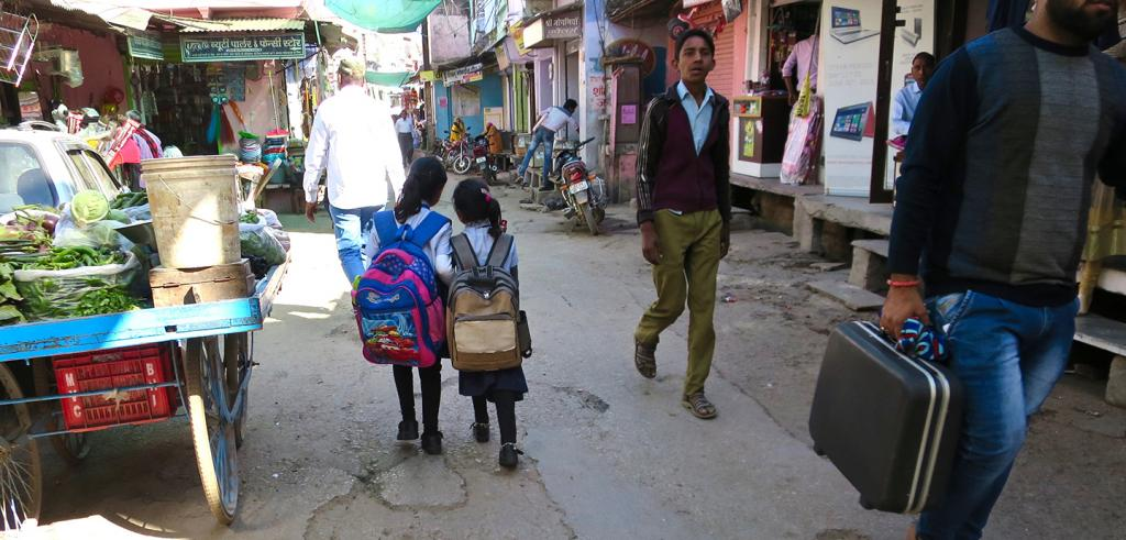 Two little girls with oversized backpacks walking down the street.