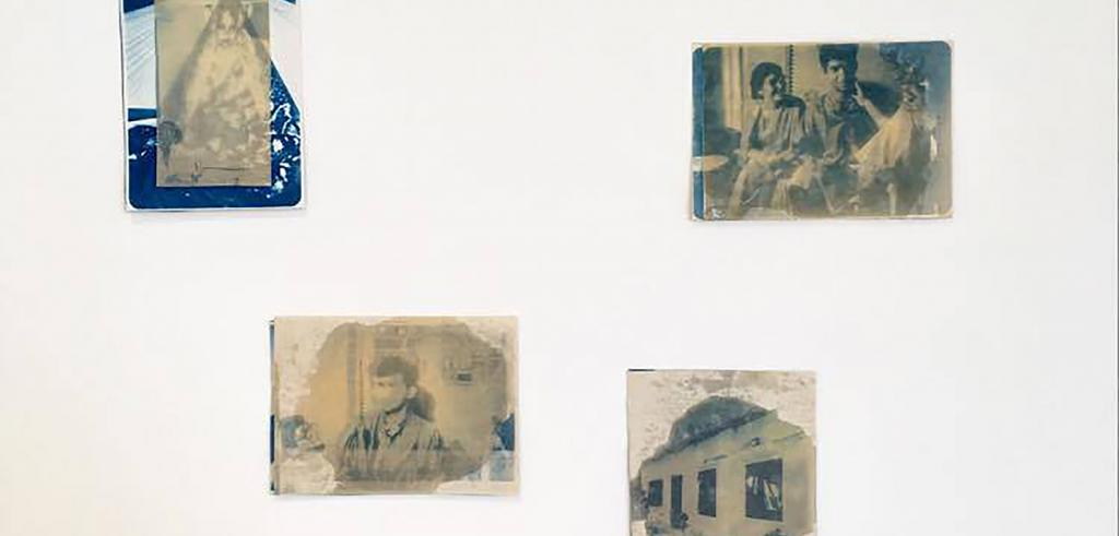 Four cyanotypes hung on a wall, featuring families and homes.