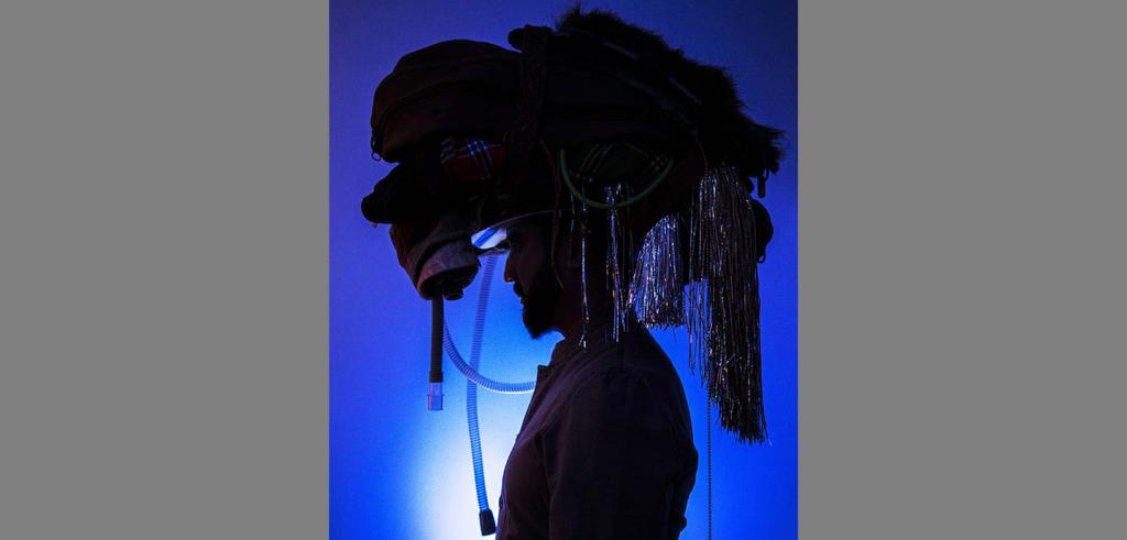 Silhouette of a man in profile wearing a large headdress over a blue background