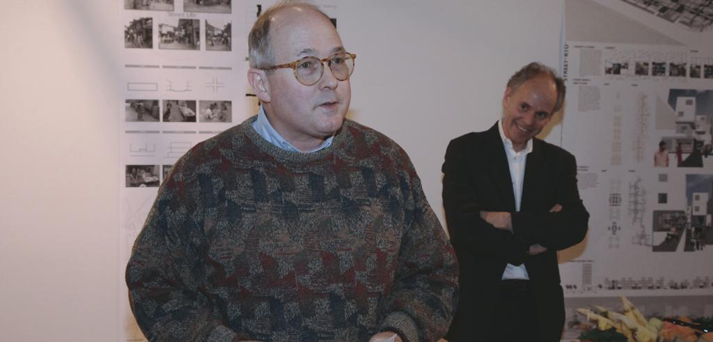 man in glasses and sweater with another man in a black blazer behind him
