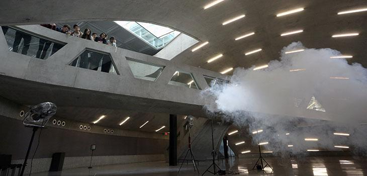 Spectators watch while Smilde works on his indoor clouds