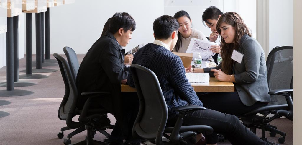 group of students and professionals sitting around a table in discussion