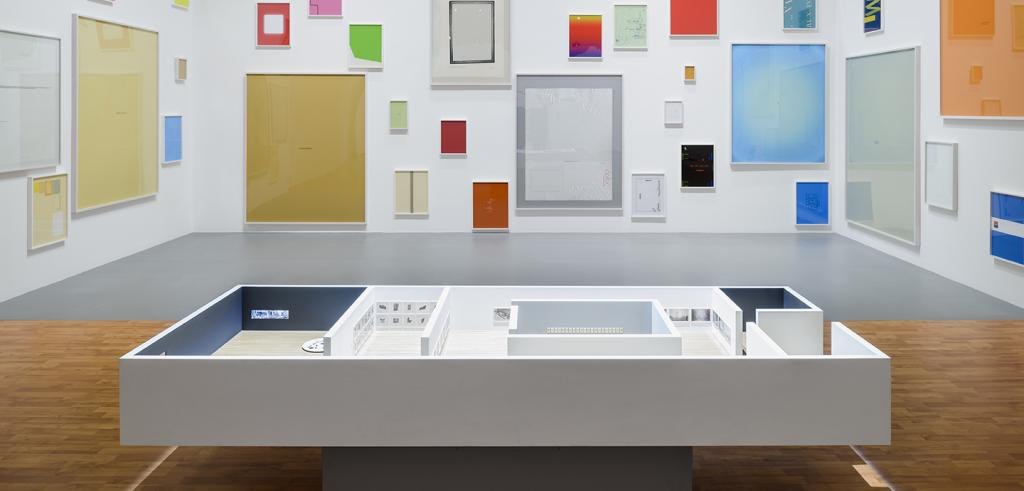 Image of an installation of bright colored rectangular pieces against a white background and a sculptural model on the floor.