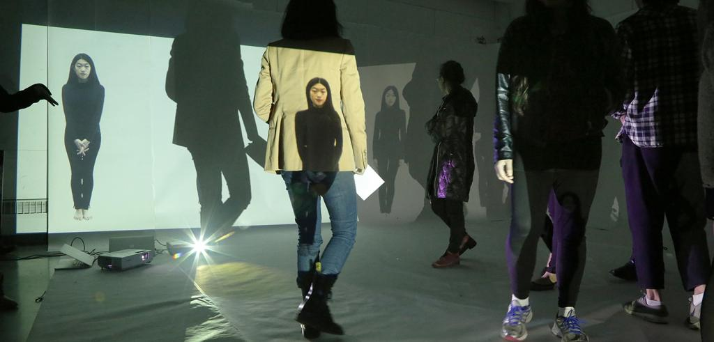people in a gallery with images projected onto their bodies