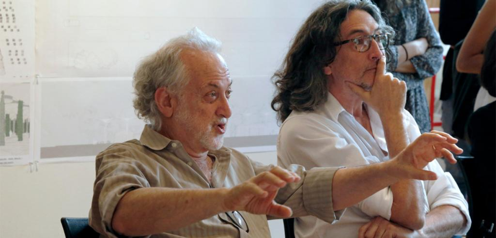 man with grey hair gesturing with hands sitting with another person with long dark hair