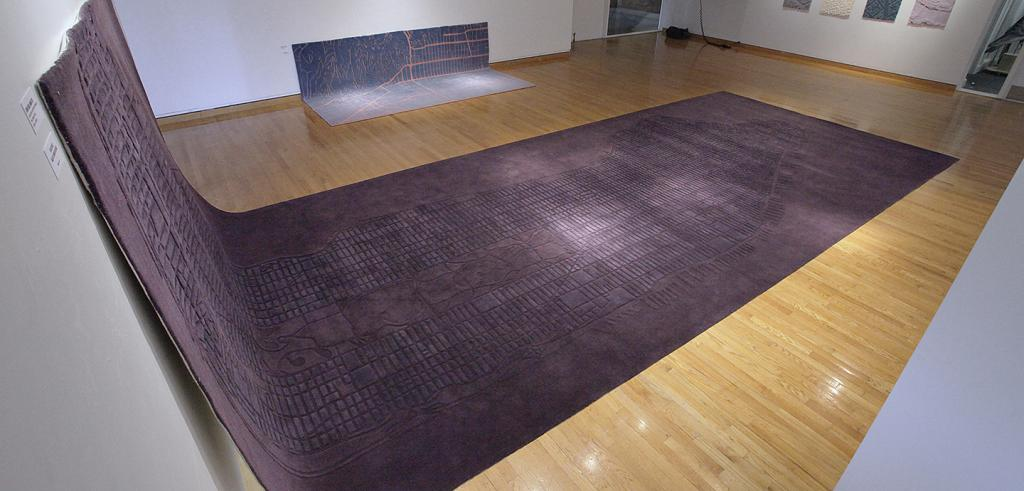 gallery showing large carpets with city maps woven into them
