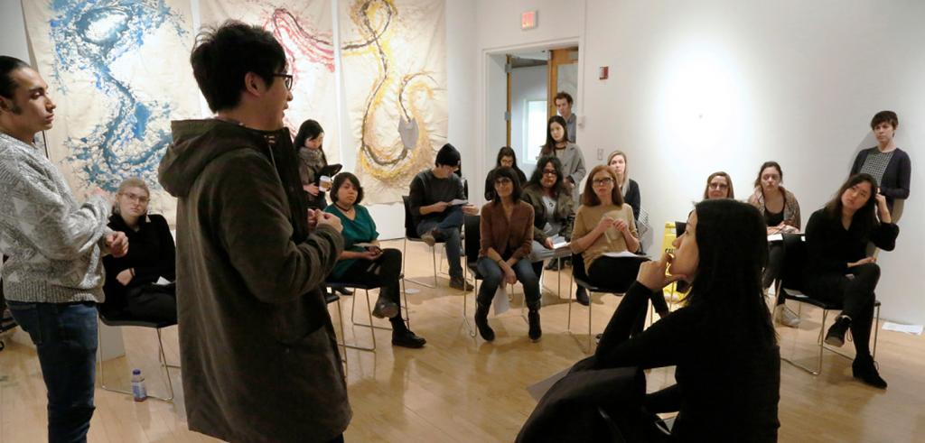 students and faculty conversing in an art gallery