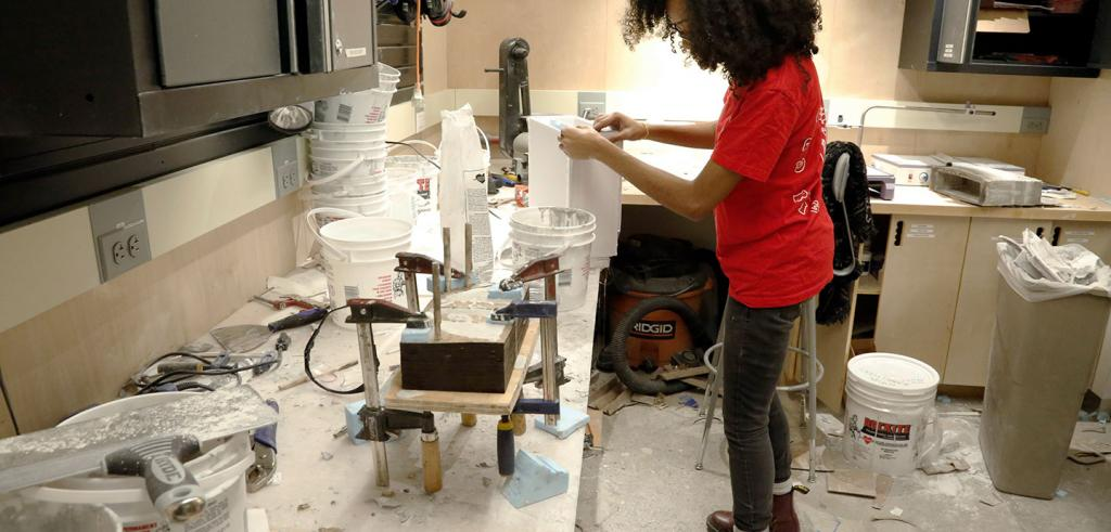 young woman in a red t-shirt working in a show with plaster and buckets and wooden models