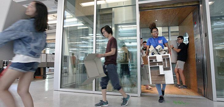 Students getting off of an elevator carrying cardboard models