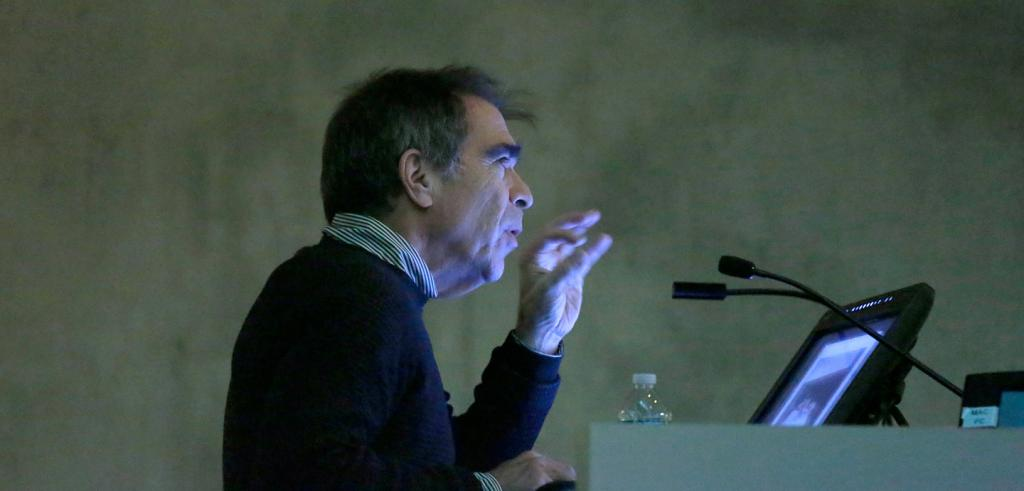 Michael Smith standing in front of a lectern during his lecture