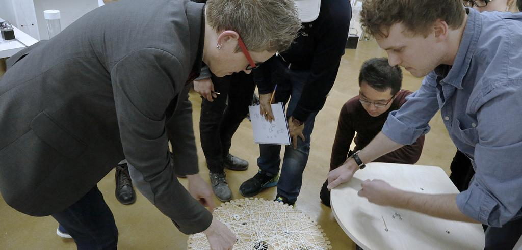 student and faculty examine a stool made of woven fabric and wood