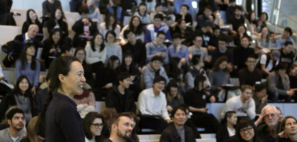 Lu Wenyu in front of a crowded auditorium