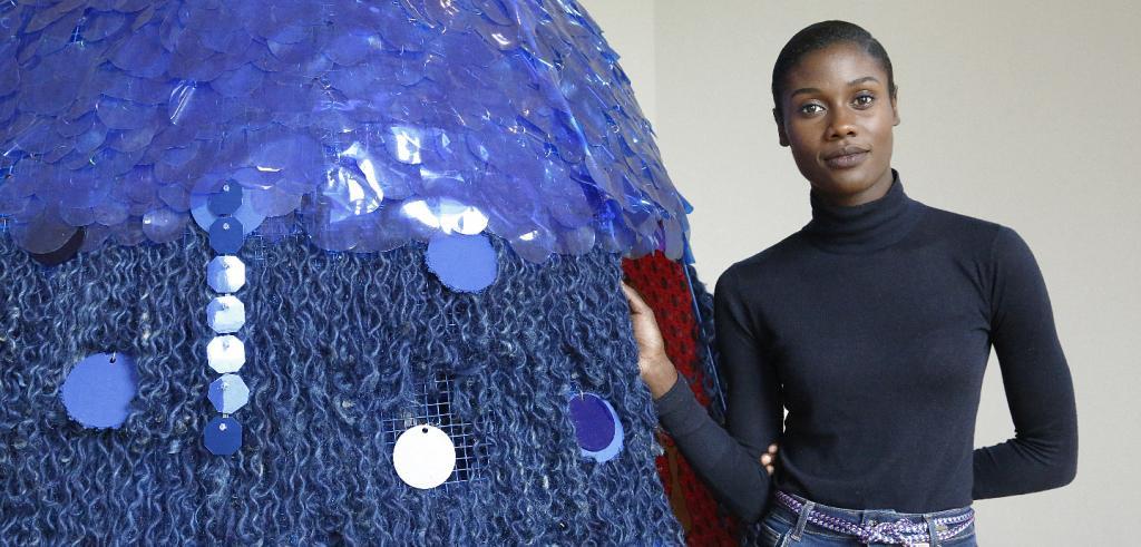 woman standing beside a blue sequined sculpture