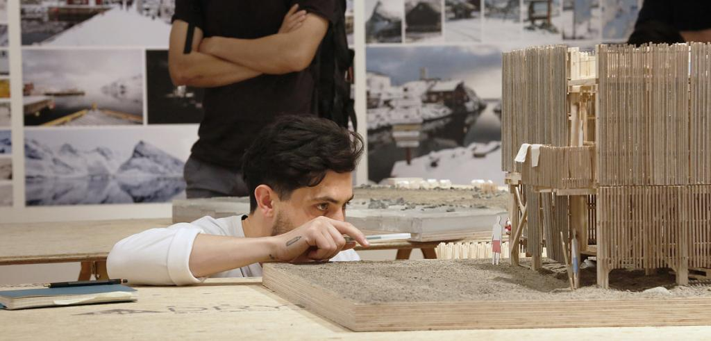 man at eye level with a wooden model