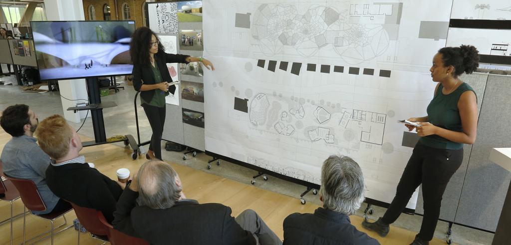 two students presenting diagrams to a group of seated critics