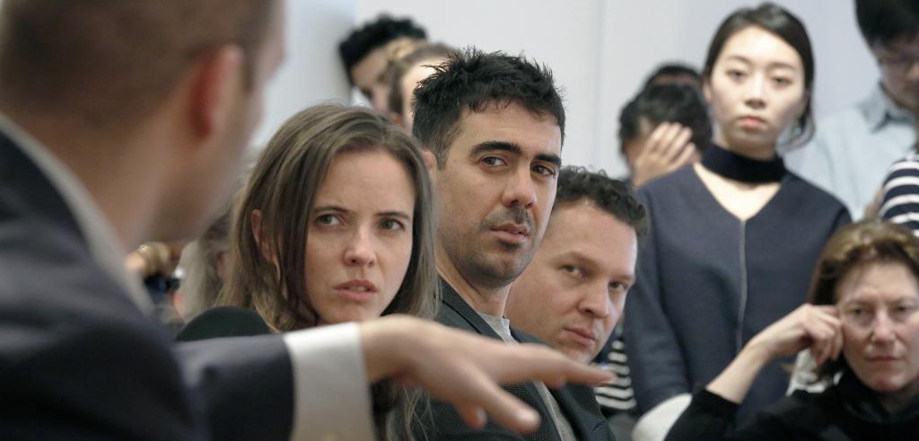 critics watch a student presentation