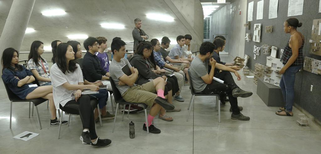 college students listening to a presentation by another student