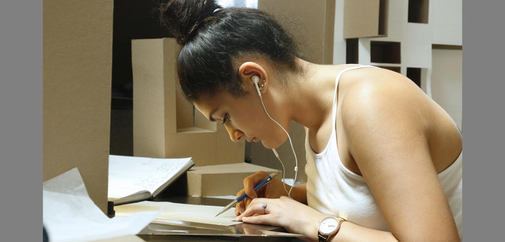 a woman wearing earbuds drawing at a desk