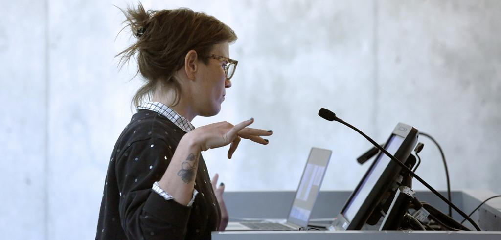 a woman at a lectern with a microphone and computer screen