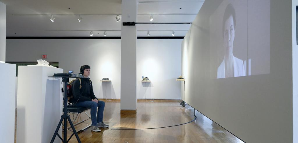 A student listens to an interactive video in Jennifer and Kevin McCoy's exhibition, Inhabiting the World We Made.