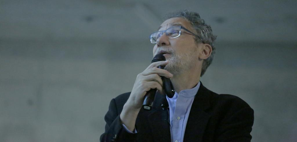 man holding and speaking into a microphone