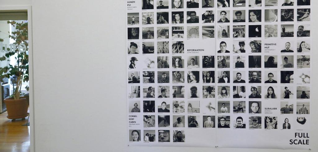 A poster on the wall next to an open doorway shows a grid of more than 100 square headshots and text in black-and-white