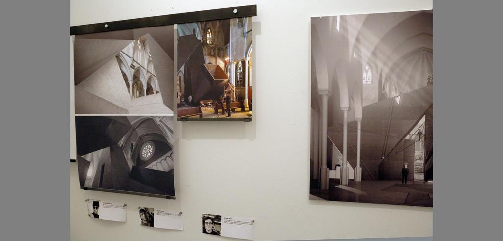Three large vertical posters depicting the inside of a church, and three smaller horizontal headshots and text are hung and pinned on a white wall
