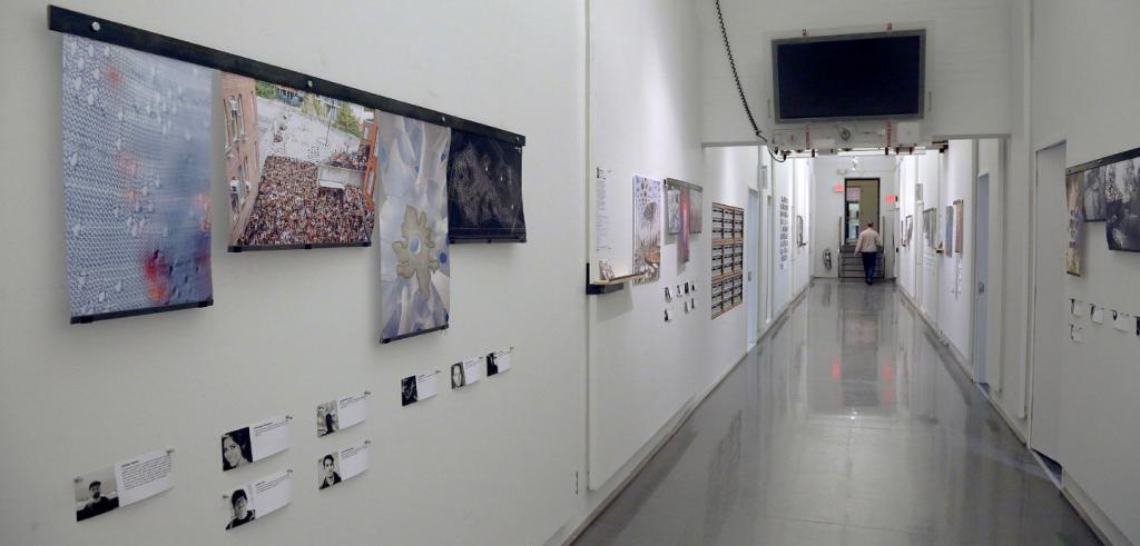 A hallway with numerous posters and photos on both walls, an overhead LCD display, and a man approaching a doorway