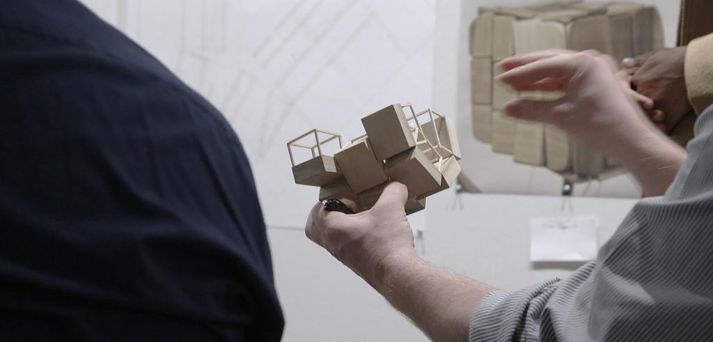 hands gesturing at wooden model