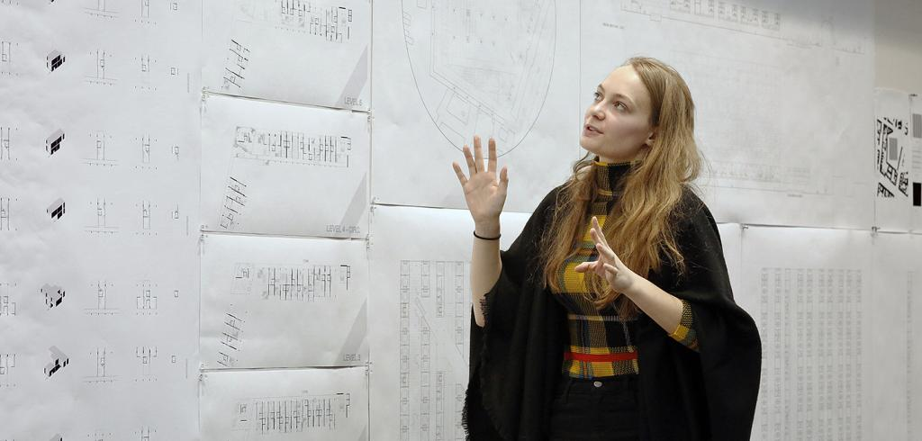 Woman wearing a black poncho looks at a wall pinned with architectural plans