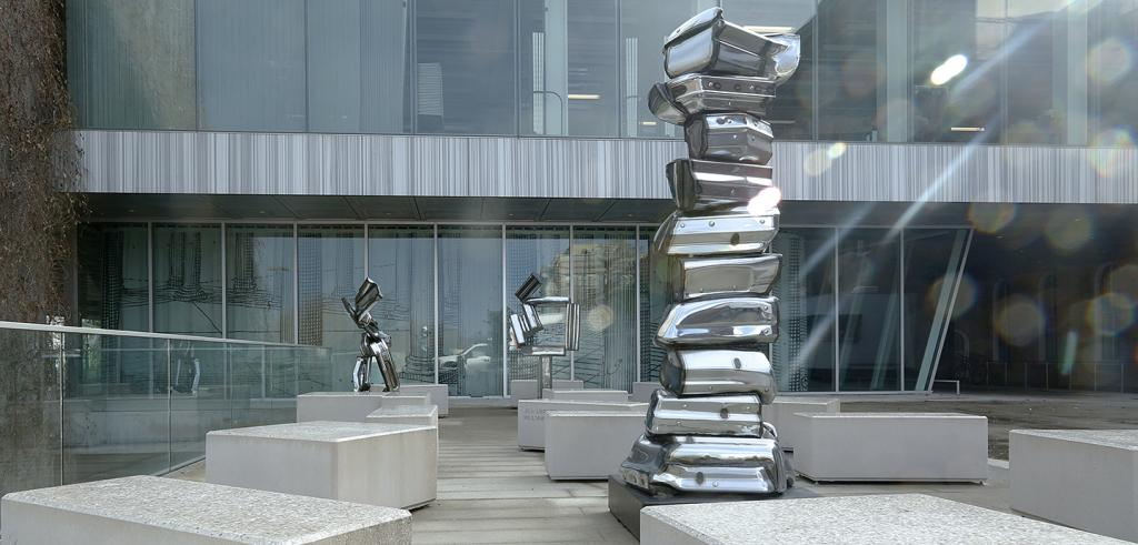 three tall, metallic sculptures made of bumpers in a courtyard with sun rays