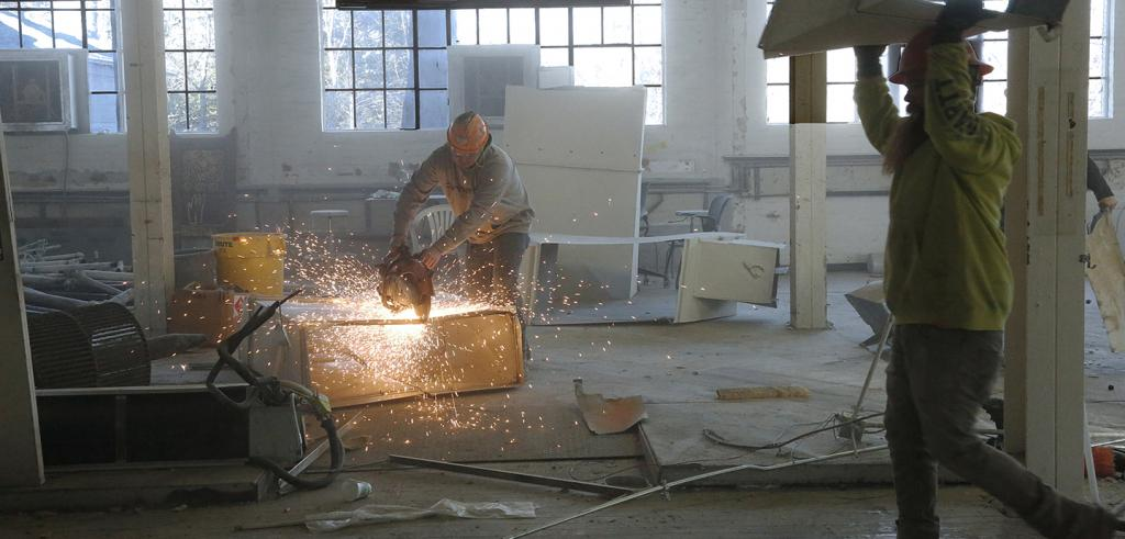 construction workers use a grinder on a piece of metal creating sparks.