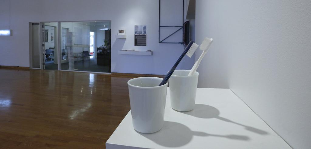 Two white china cups with toothbrushes in a large room with white walls.