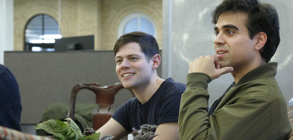 Two men smiling and seated in a room.