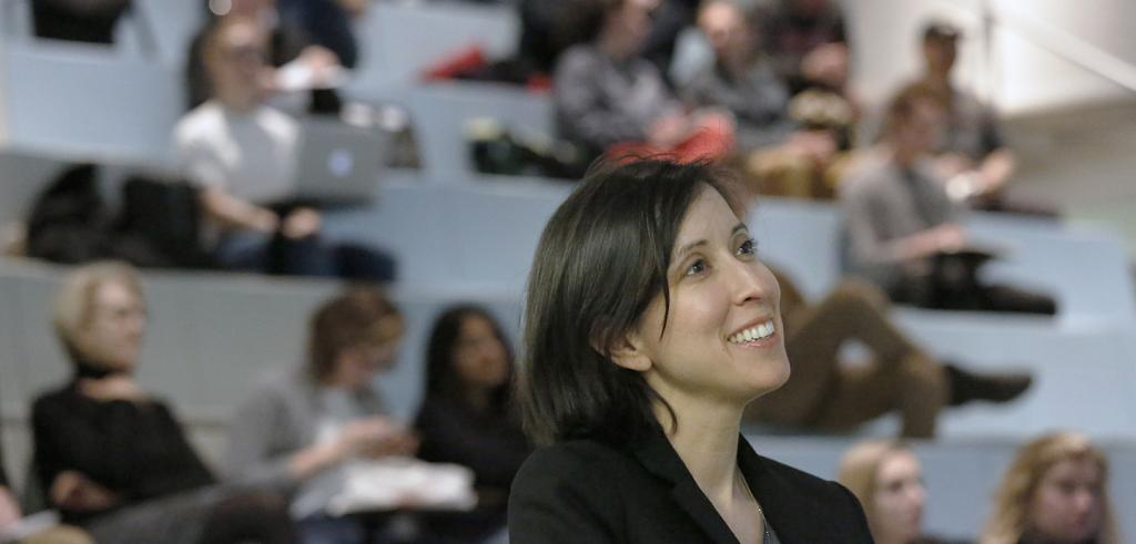 Head and shoulders view of a woman smiling and seated in an auditorium.