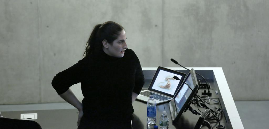 Woman with her right hand resting on her hip, standing at a lecturn with microphones and monitor screens.
