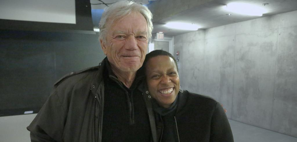Man with white hair and dark green jacket poses with african american woman smiling and leaning on the mans shoulder.