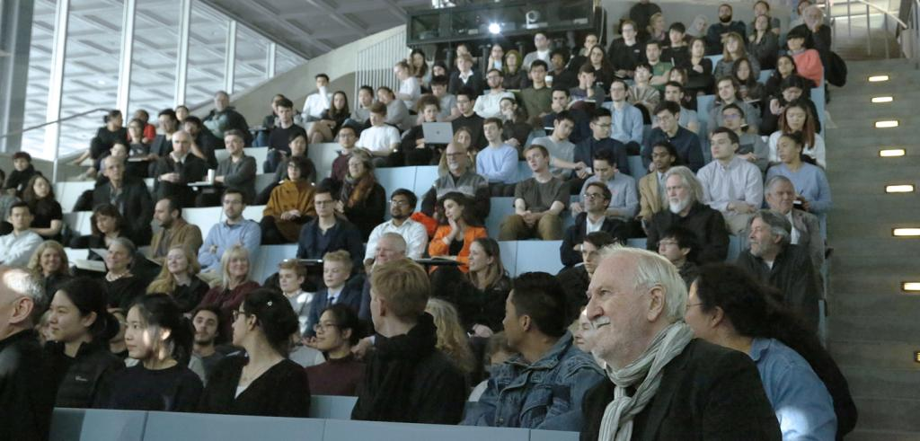 Man with gray hair and scarf (lower right), sitting in an auditorium, surrounded by a group of men and women.