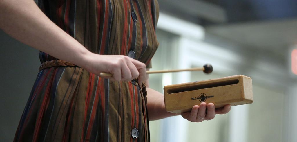 A close-up view of a woman's hands holding a percussion instrument.