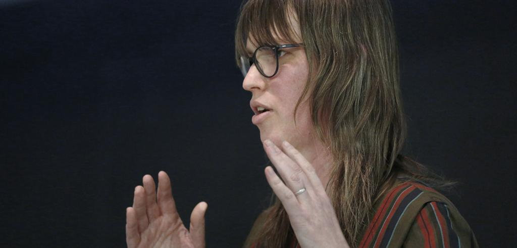 Woman with long hair and glasses, gesturing with her hands and speaking.