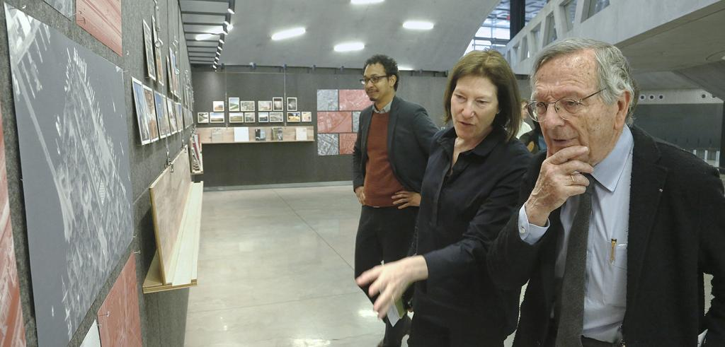two people in the foreground looking at pictures on a wall
