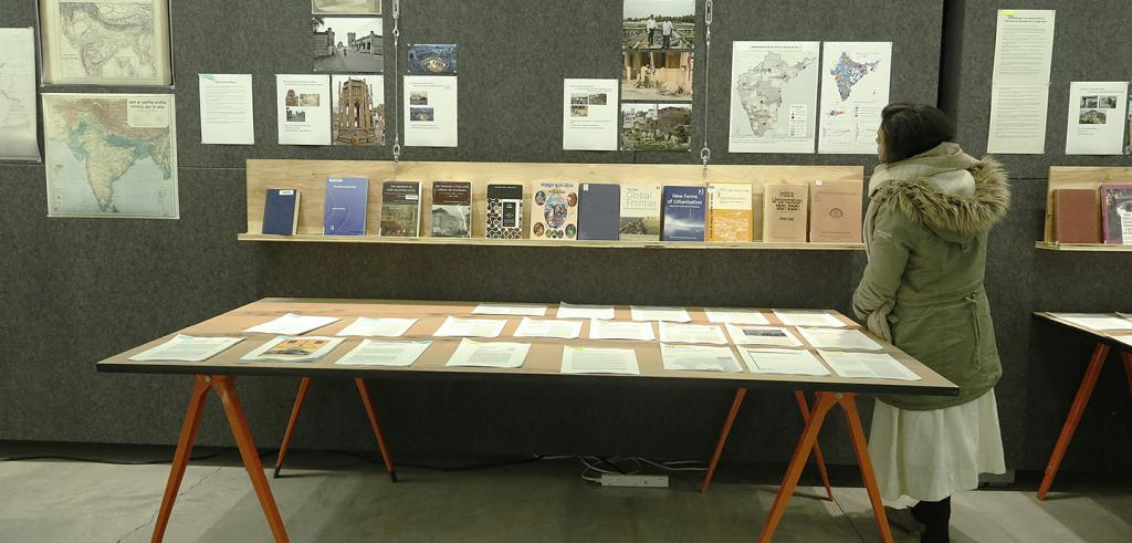 A woman looks at a display of books, articles and maps on a wall and a table