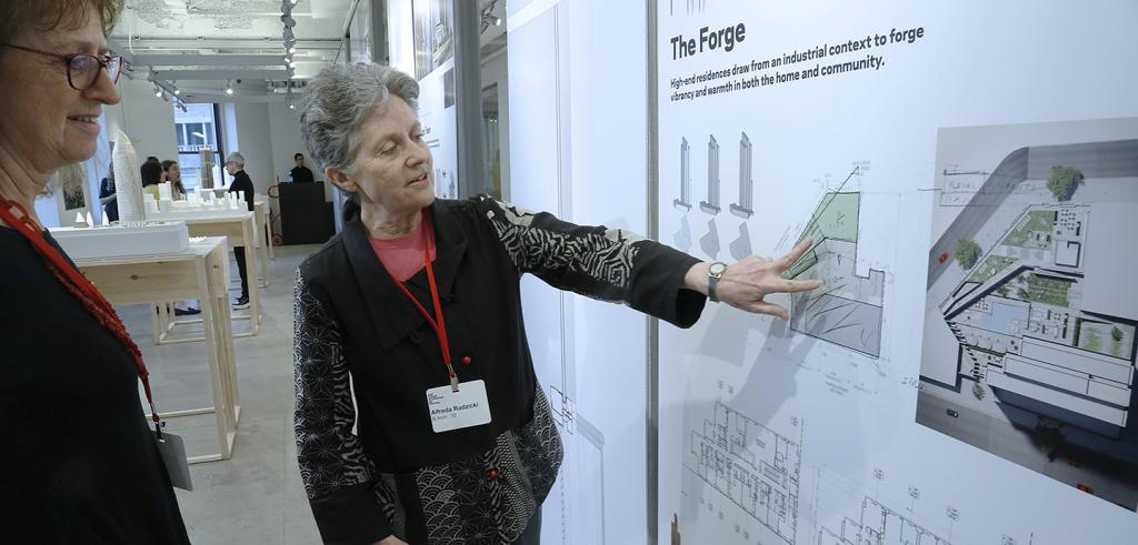 Two women looking at architecture drawings on a wall in a gallery as one points at a drawing