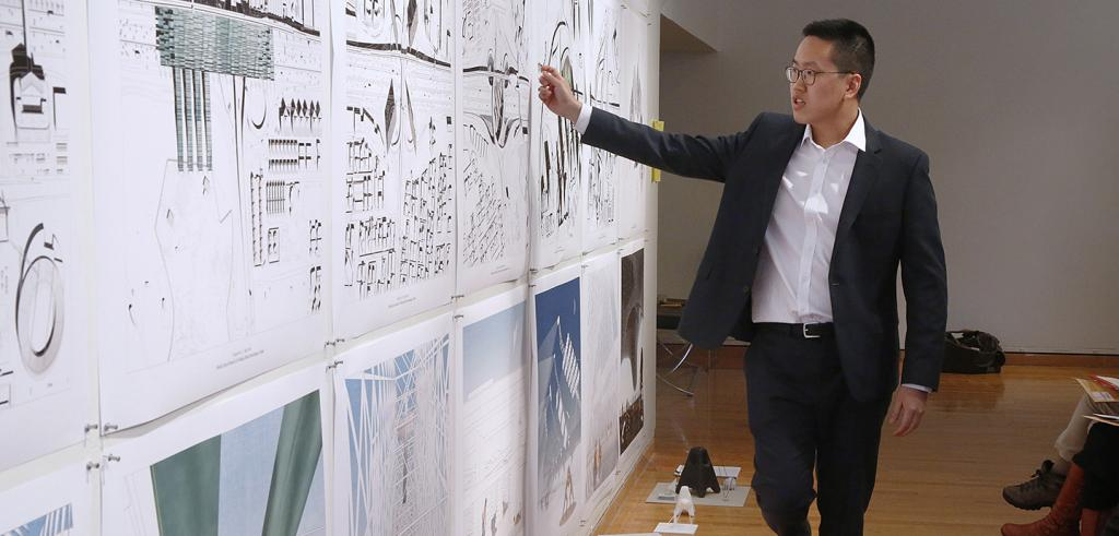 man wearing a black suit and a white shirt points at a wall of architectural drawings