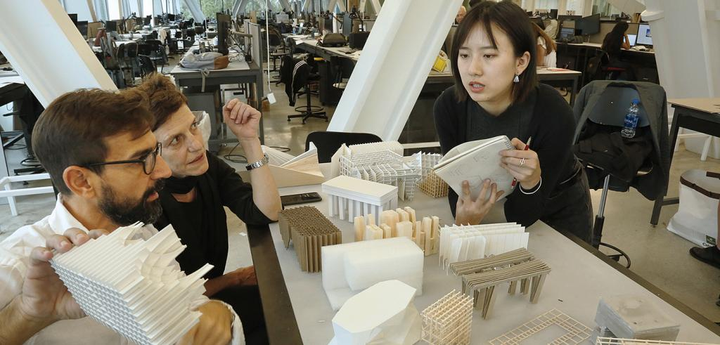 Three people in a studio discussing architectural models