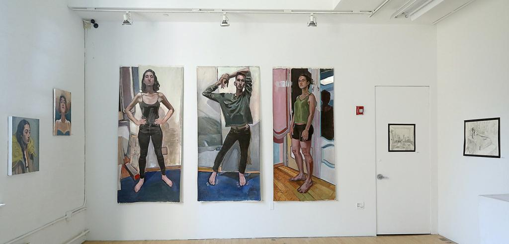three tall paintings of individuals hung on a gallery wall with smaller works around them