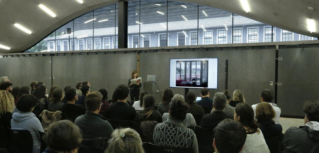 Woman standing in front of a crowd reading from a book with an LCD screen to her left and a window behind her.
