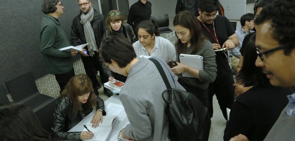 Woman in lower left corner of the frame writing in a book as people gathered around watch.