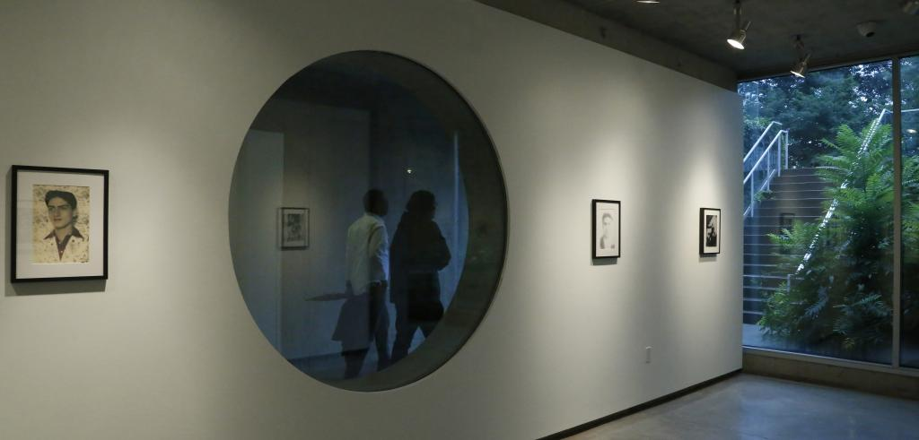 A gallery wall with a round window with three small photographs on the wall an outdoor staircase on the right and two figures walking on the other side of the window.